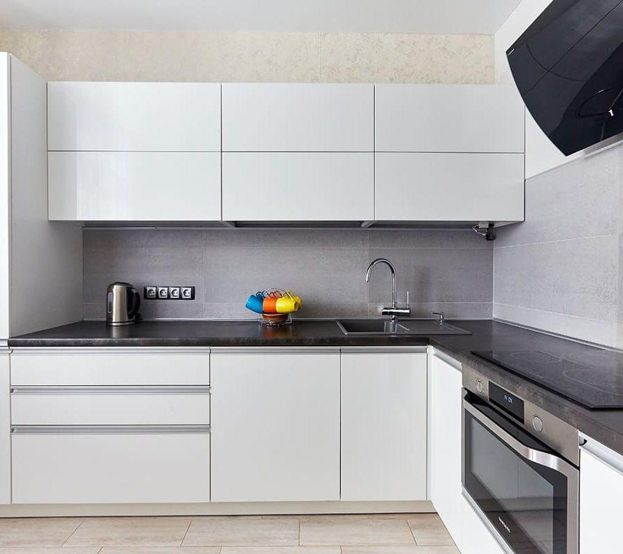 современная белая кухня с черной столешницей